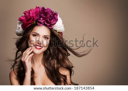 portrait of beautiful young woman with flower wreath on her head and red lips, with hand near her face, posing in studio.  - stock photo