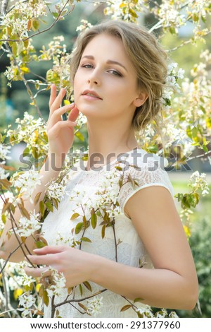 Portrait of beautiful young woman with flowers in hair. Make up and hair style. Wedding bride make up.