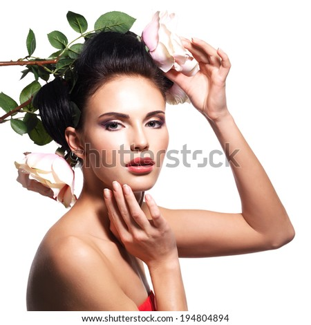 Portrait of beautiful young woman with flowers in hair touching her face - isolated on white - stock photo