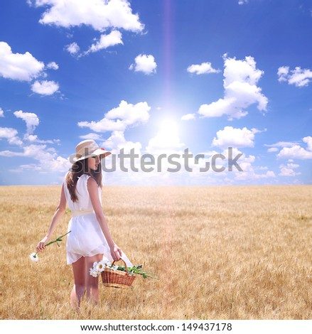 Portrait of beautiful young woman with flowers in the field - stock photo