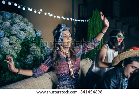 Portrait of beautiful young woman with funny moustache and necktie dancing and having fun in a outdoors party. Friendship and celebrations concept. - stock photo