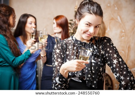 Portrait of beautiful young woman with glass of champagne celebrating new year with friends - stock photo