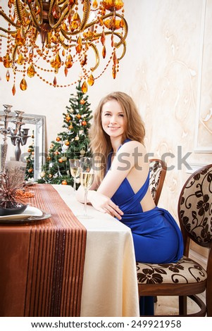 Portrait of beautiful young woman with glass of champagne over christmas background - stock photo