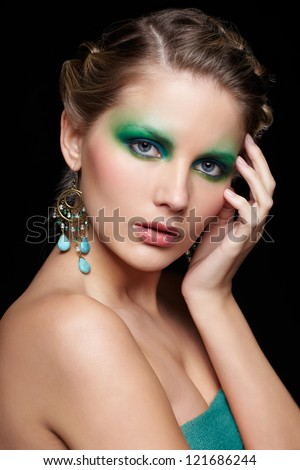 portrait of beautiful young woman with green and blue eye shade make up touching head