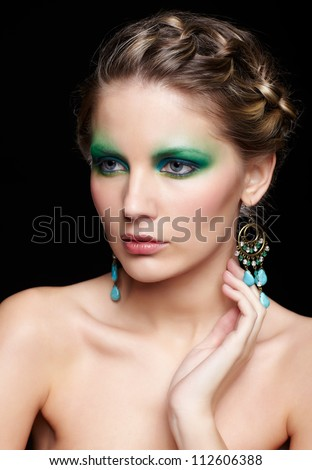 portrait of beautiful young woman with green and blue eye shade make up touching her neck