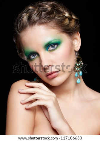 portrait of beautiful young woman with green and blue eye shade make-up touching her shoulder