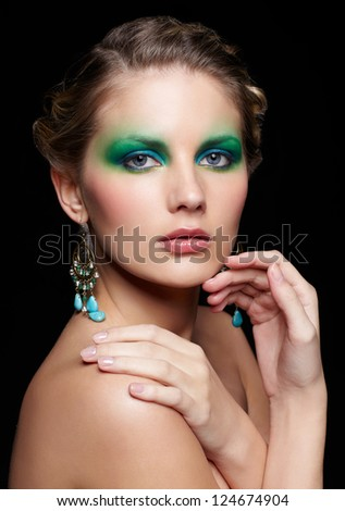 portrait of beautiful young woman with green and blue eye shade make up touching shoulder and chin