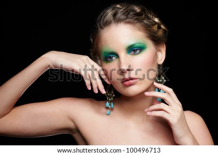 portrait of beautiful young woman with green and blue eye shade makeup touching face and neck