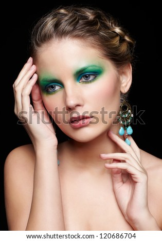 portrait of beautiful young woman with green and blue eye shade makeup touching head and neck