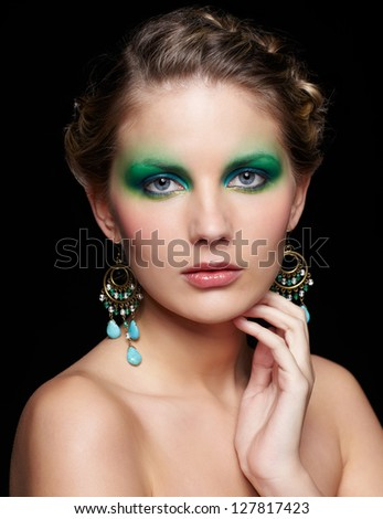 portrait of beautiful young woman with green and blue eye shade makeup touching her neck