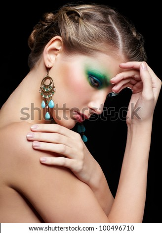 portrait of beautiful young woman with green and blue eye shade makeup touching her shoulder and forehead