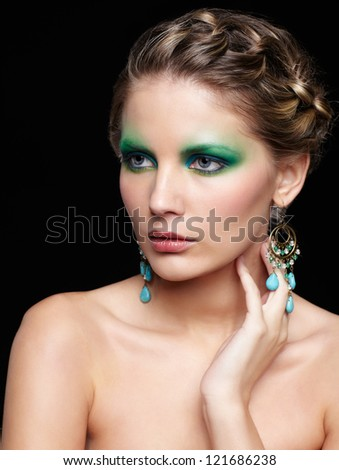 portrait of beautiful young woman with green and blue eye shade makeup touching neck