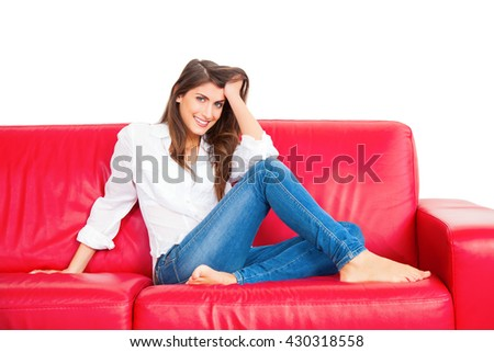 Portrait of beautiful young woman with hand in hair. Full length of happy female is relaxing on red sofa. She is with confident look on her face isolated over white background. - stock photo