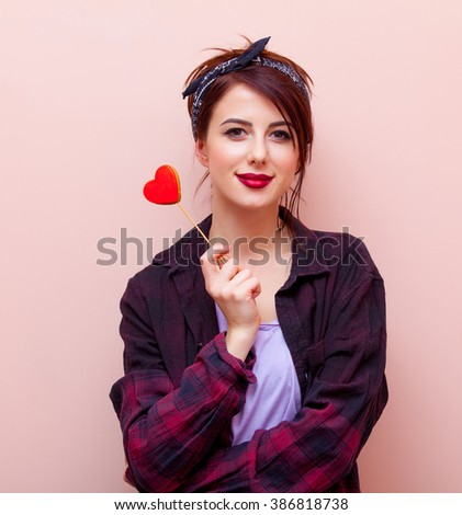 portrait of beautiful young woman with heart-shaped toy standing on the pink background - stock photo