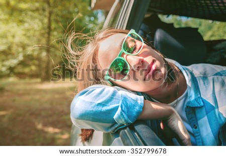 Portrait of beautiful young woman with her head over a open window car during a travel. Relax and nature concept. - stock photo