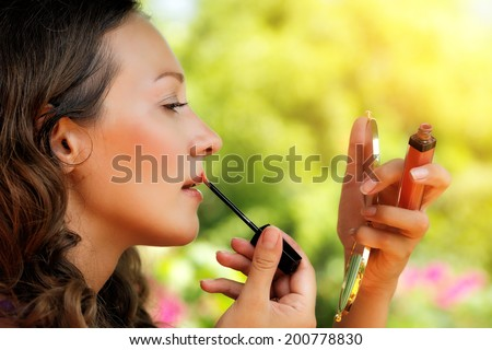 Portrait of beautiful young woman with lip gloss and mirror, against green of summer park. - stock photo
