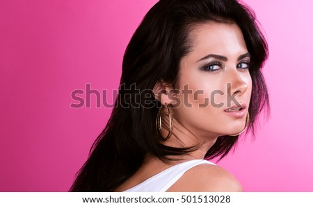 Portrait of beautiful young woman with long black hair. Delicate look and Fashion shiny highlighter on skin. Neutral pink background