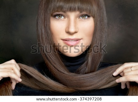 Portrait of beautiful young woman with long brown hair on dark background
