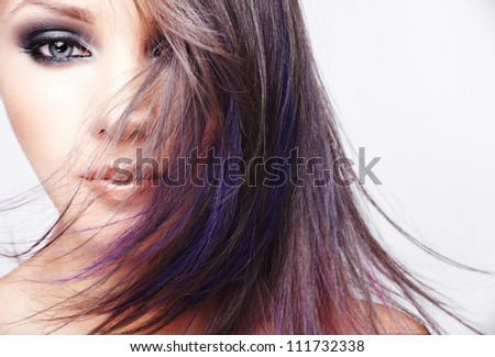 Portrait of beautiful young woman with long colored brown hair and bright make-up - stock photo
