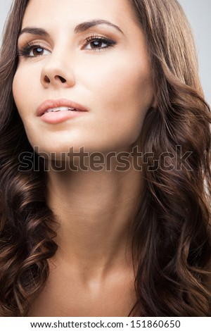 Portrait of beautiful young woman with long curly hair, over grey background