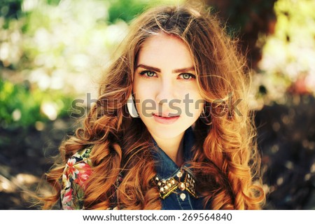 Portrait of beautiful young woman with long curly hair wearing fashionable clothes. Closeup face of a pretty caucasian model looking at camera. Fashion photo outdoors, lifestyle - stock photo
