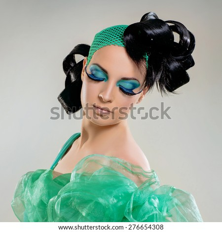 Portrait of beautiful young woman with long eyelashes, green colored eye lids black and styled hair.