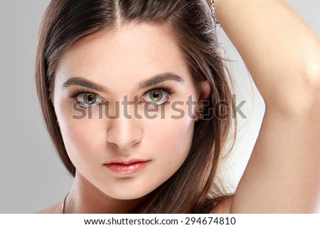 portrait of beautiful young woman with long hair and her hand at her head - stock photo