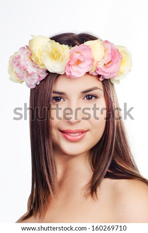 Portrait of beautiful young woman with long hair in a circlet of eustoma flowers, isolated on white background