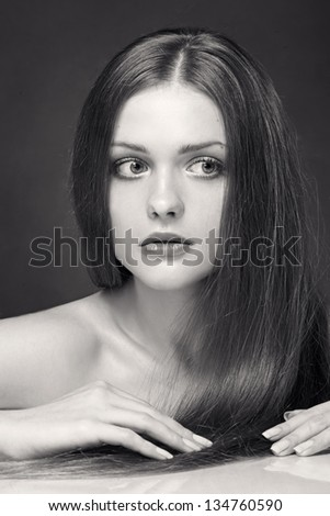 Portrait of beautiful young woman with long straight brown hair. Black and white - stock photo