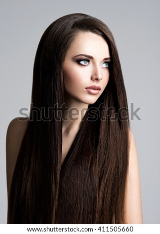 Portrait of beautiful young woman with long straight  hair at studio