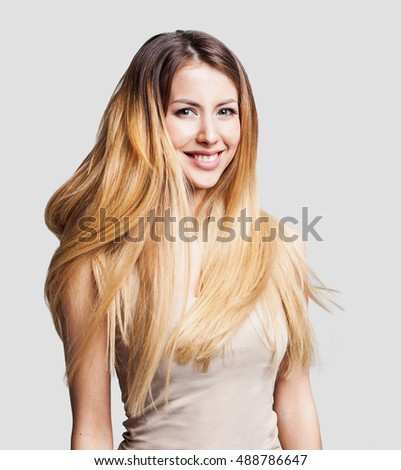 Portrait of beautiful young woman with long waving hair. Isolated on gray background