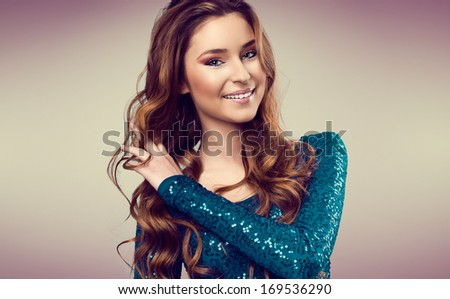 Portrait of beautiful young woman with long wavy hair and nice make up. Fashion - stock photo