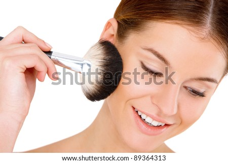 Portrait of beautiful young woman with makeup brush on white