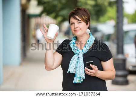 Portrait of beautiful young woman with mobilephone and disposable coffee cup waving - stock photo