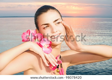 Portrait of beautiful young woman with orchid against sea sunset.