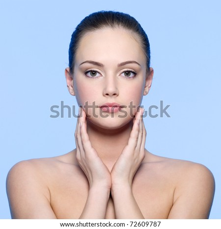 Portrait of beautiful young woman with  perfect  skin - blue background - stock photo