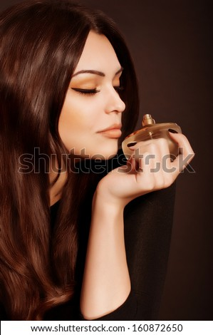 Portrait of beautiful young woman with perfume bottle - stock photo