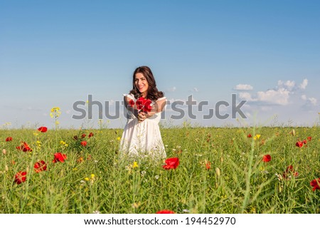 Portrait of beautiful young woman with poppies in the field holding a poppies bouquet
