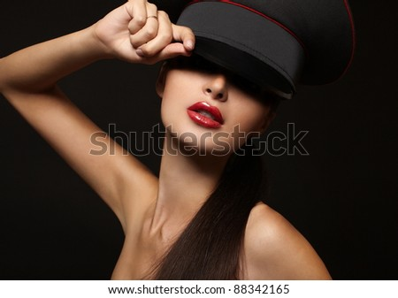 Portrait of beautiful young woman with red lips on black background