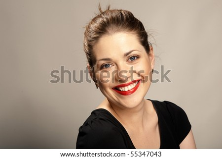 Portrait of  beautiful young woman with red lips  over gray. Big toothy smile. - stock photo
