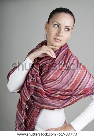 Portrait of beautiful young woman with red scarf, isolated on gray background - stock photo