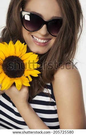 Portrait of beautiful young woman with sunflower and brown hair wearing fashion sunglasses - stock photo