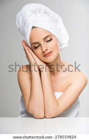 Portrait of beautiful young woman with towel on head, closing her eyes. - stock photo