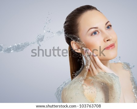 Portrait of beautiful young woman with water splashes - stock photo