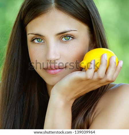 Portrait of beautiful young woman with yellow lemon, against background of summer green park.