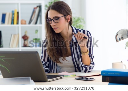 Portrait of beautiful young woman working in the office. - stock photo