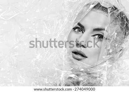 Portrait of beautiful young woman, wrapped in cellophane, black and white