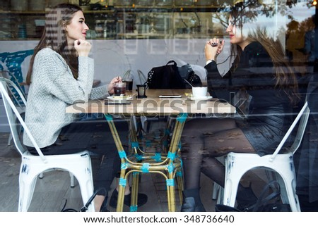 Portrait of beautiful young women drinking tea in a coffee shop - stock photo