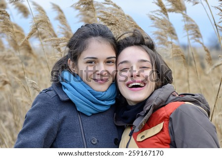Portrait of beautiful young women in field - stock photo