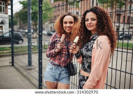 Portrait of beautiful young women standing against a fence looking at camera while eating ice cream.